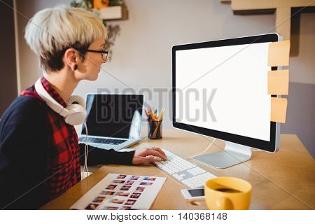 Female graphic designer working on computer at office