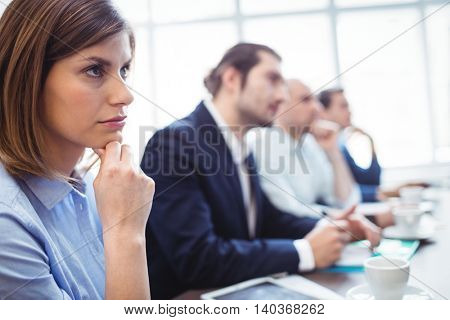 Thoughtful businesswoman with colleagues during meeting at creative office