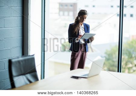 Young woman using digital tablet against window in creative office
