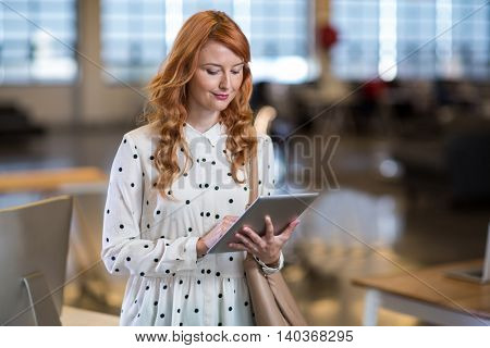Young woman using digital tablet in office