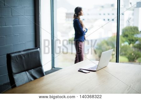 Young woman standing at window in creative office