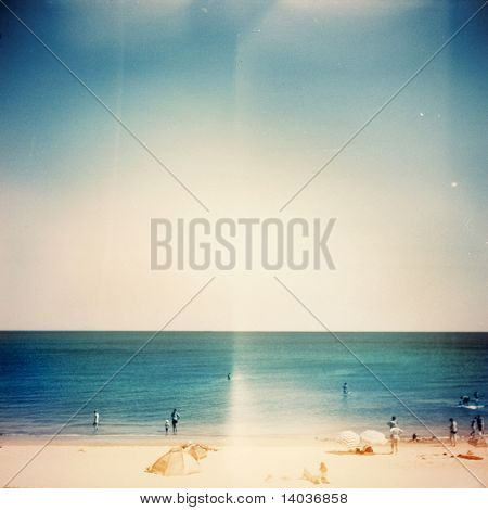 Retro medium format photo. Sunny day on the beach. Grain, blur added as vintage effect.