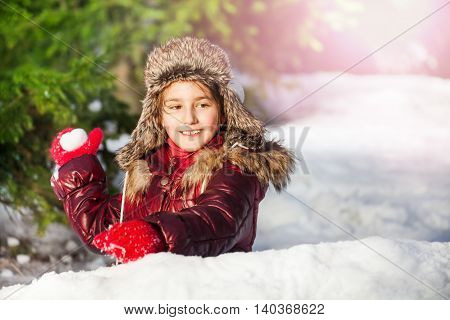 Cute girl having fun with snowball fight at the winter forest