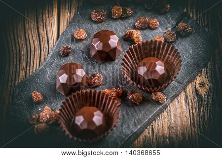 Chocolate sweets with raisin on black slate