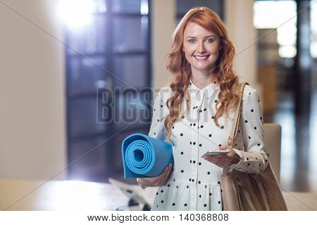 Portrait of smiling woman holding mobile phone and folded mat in office