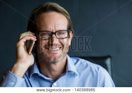 Portrait of smiling businessman talking on phone in office