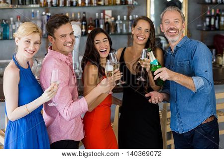 Group of friends holding glass of champagne flute and bottle in restaurant