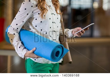 Midsection of woman using mobile phone in creative office