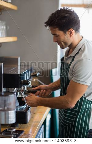 Waiter making cup of coffee at cafe