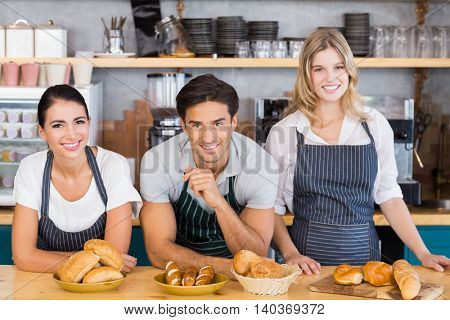 Smiling waiter and two waitresses leaning on counter at cafe