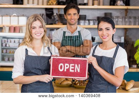 Smiling colleagues showing signboard with open sign in cafe