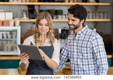 Smiling man and waitress standing at counter using digital tablet in cafe