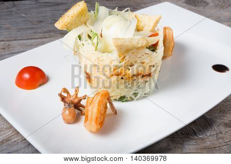 Seafood salad with croutons served on a white plate