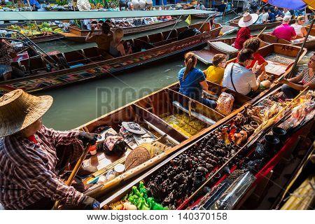 Damnoen Saduak Thailand-20 March 2016. Busy sunday morning at Damnoen Saduak floating market Ratchaburi Thailand place of locals selling fresh produce cooked food and souvenirs.