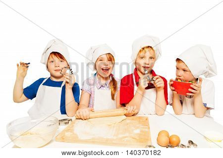 Four young bakers, kids in aprons and toques standing in row, making dough for homemade cookies, isolated on white