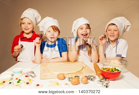 Four happy little chefs, sitting in a row and playing bakers, holding cookie cutters for homemade cookies