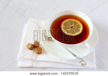 Black tea with lemon in a white bone china cup