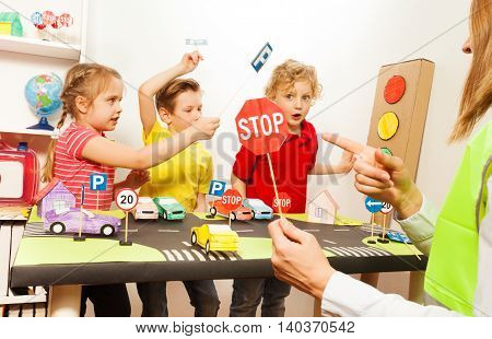 Group of three kids, preschool boys and girl having fun teaching traffic signs and female teacher pointing to a Stop sign icon in road safety class