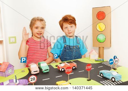 Two happy preschoolers, five years old boy and girl studying road traffic regulations in the kindergarten