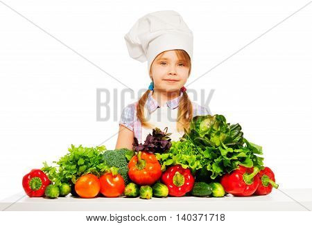 Young cook, girl in white apron and toque standing with fresh vegetables, isolated on white