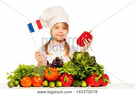 Smiling girl in cook's uniform holding French flag and fresh red pepper, isolated on white