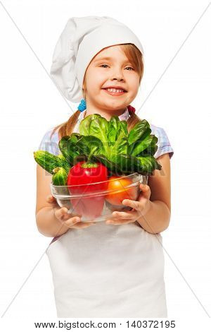 Close-up picture of young smiling cook, girl with bowl full of fresh vegetables, isolated on white
