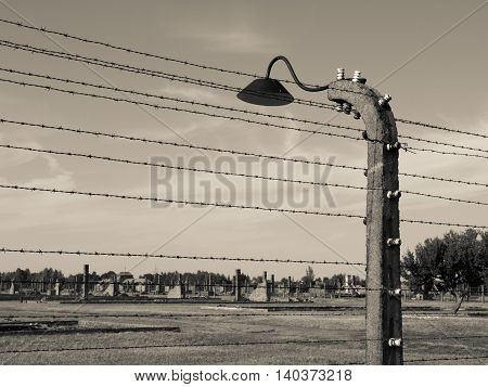 Barb wire fence with lamp in former German Nazi concentration and extermination camp Auschwitz Birkenau, Poland
