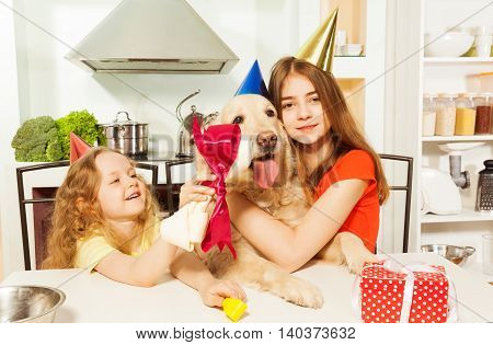 Two cheerful sisters in party hats giving present for their pet - tasty bone with pink bow, sitting in the kitchen
