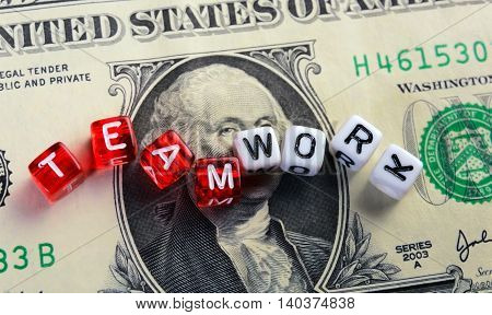 dices with text TEAMWORK on a dollar banknote