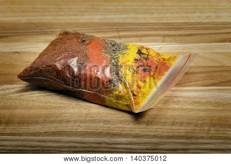 package set of spices for pilaf on a wooden cutting board