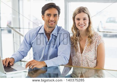 Portrait of happy couple using laptop in cafe