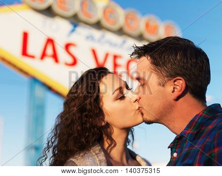 couple having romantic kiss in front of the welcome to las vegas sign