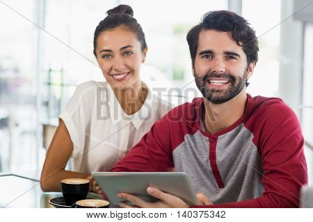 Portrait of smiling couple using digital tablet in cafe