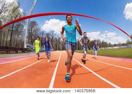 Happy African sprinter, teenage boy in sportswear, running to the finish line on the stadium