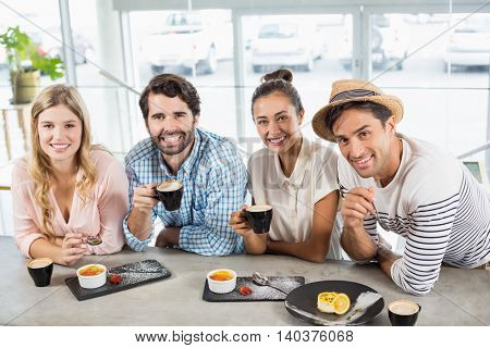 Group of happy friends having cup of coffee in cafe