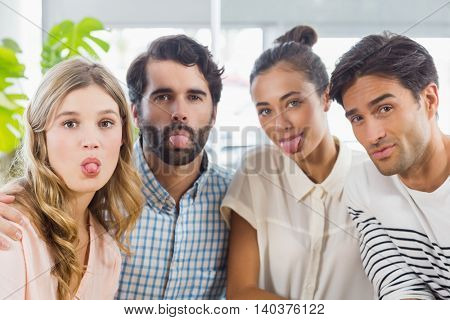 Portrait of friends sticking out tongue in cafe