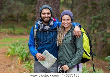 Portrait of happy hiker couple standing with arm around at countryside