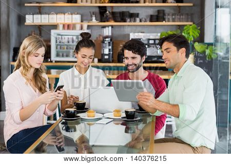 Group of friends using mobile phone, digital tablet and laptop in cafe