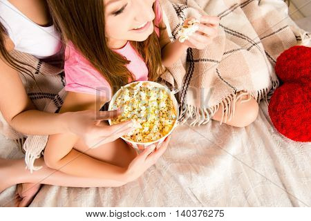 Close Up Of Two Sisters Lying In Bed And Eating Popcorn