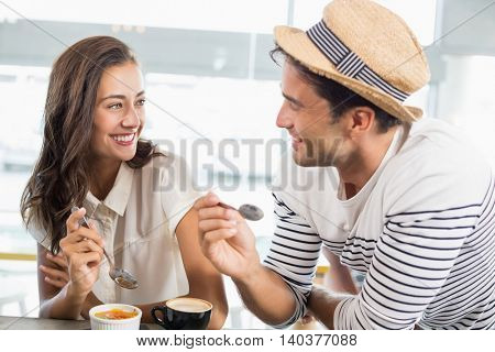 Smiling couple having dessert in cafe