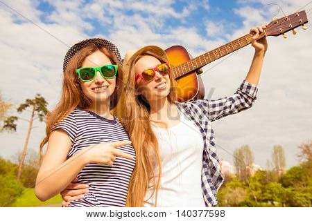Two Pretty Girls In Glasses And Hats Having Walk With Guitar