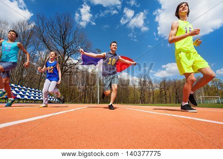 Teenage boys and girl, race winners, running with flag of France on the track