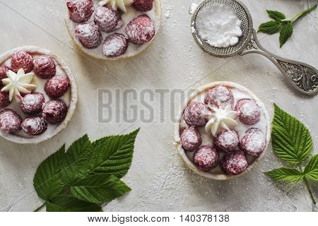 Sweet small french tarts with fresh raspberry and cream over vintage stone table