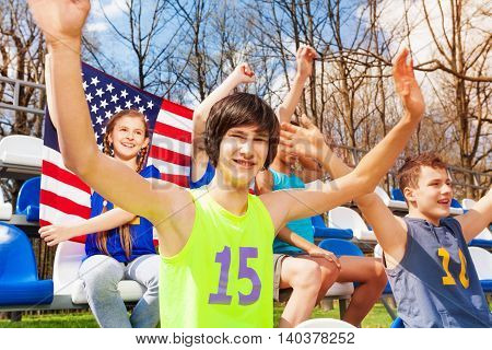 Portrait of multiethnic teenage sport supporters watching the game, sitting on the tribune and holding flag of America