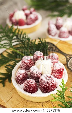 Sweet small french tarts with fresh raspberry and cream. Selective focus