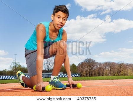 Teenage African sporty boy picking up two dumbbells, kneeling on track in the stadium