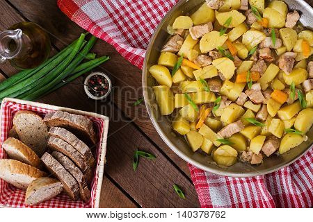Stewed Potatoes With Meat In A Frying Pan On A Wooden Table. Top View