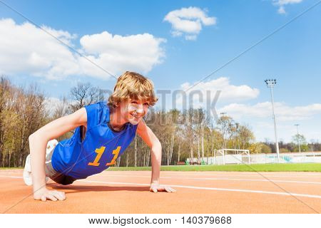 Sporty smiling teenage boy doing push-ups exercises outdoor in the stadium