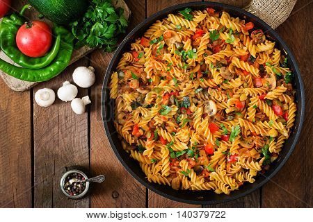 Vegetarian Vegetable Pasta Fusilli With Zucchini, Mushrooms And Capers In Pan On Wooden Table. Top V