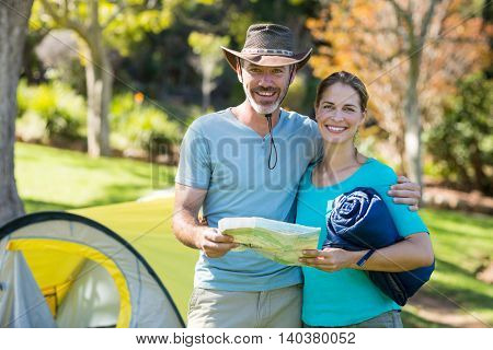 Portrait of happy hiker couple holding map in forest